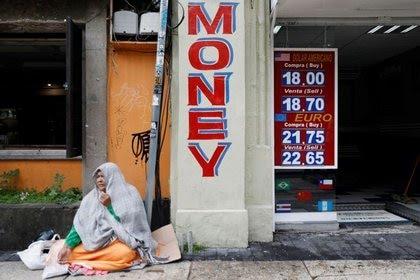 Una mujer pide dinero junto a la cotización del peso mexicano frente al dólar en una casa de cambio en Ciudad de México(Foto: Reuters/Edgard Garrido)