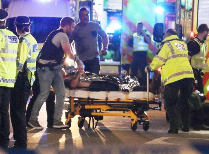 Armed police are pictured helping a victim who is being stretchered into an ambulance