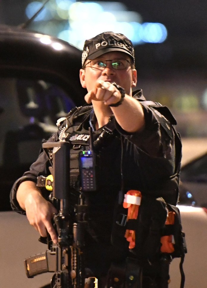 An armed police pictured urging people to flee the area at London Bridge