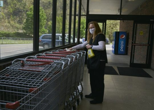 Foodland in Gilbert, West Virginia, is the only grocery store in Mingo County. Drema Curry sanatizes carts. Photo: Stacy Kranitz/100 Days in Appalachia