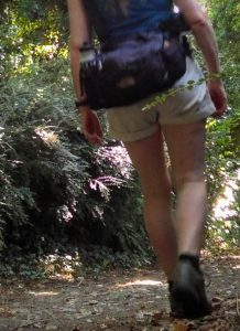 Beginner hikers can be overwhelmed with the choice of day sacks on offer. This walker is shown from behind wearing a lumbar pack, which is plenty big enough for a summer day walk.