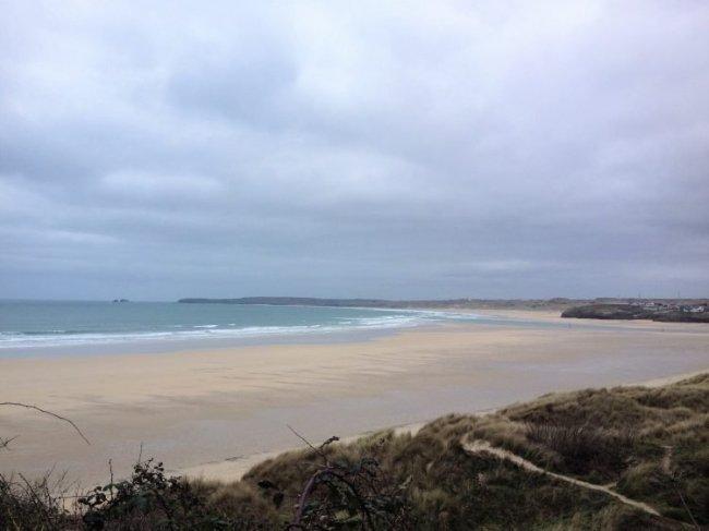 Wide sandy beach under grey skies. South West Coast Path.