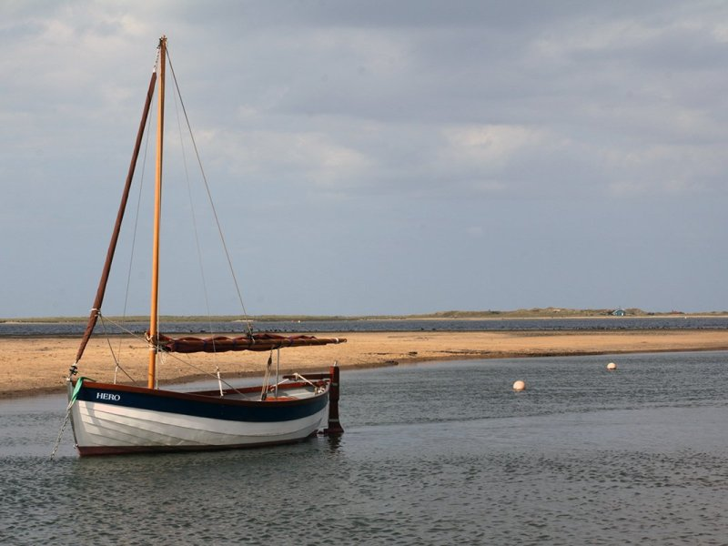 Small sailing boat on the water, UK. Norfolk Coast Path National Trail. Copyright Stephanie Boon, 2018. All Rights Reserved.