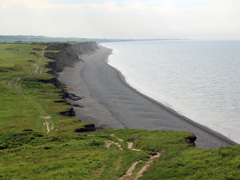 Looking along a grey stone beach and the coastal path, from the top of a cliff. Norfolk Coast Path National Trail, UK. Copyright Stephanie Boon, 2018. All Rights Reserved.