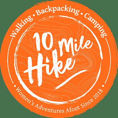 10 Mile Hike logo. Circular. Orange background, white text: 10 Mile Hike, Walking, Backpacking, Camping,Women's Adventures Afoot Since 2018