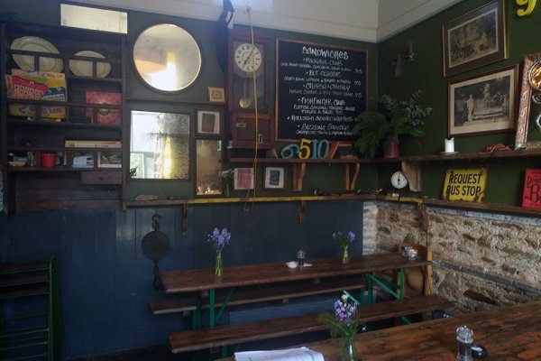 Cafe interior showing school-style benches and vintage fittings.