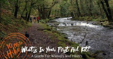Featured Image: What's in Your Outdoor First Aid Kit, A Guide For Walkers And Hikers. 3 walkers and a dog walking beside a river in woodland near Dartmoor, Devon