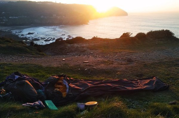 Bivi bag laid out on the cliff tops at sunset