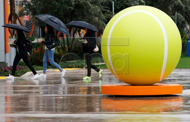 People walk on the grounds past a giant tennis ball during a rain delay at the Miami Open tournament in Miami, Florida, USA, 19 March 2019.  EPA-EFE/JASON SZENES