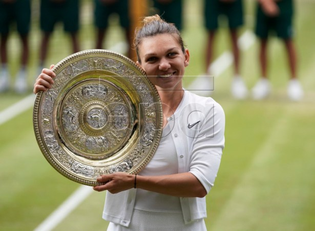 Simona Halep of Romania with the championship trophy as she celebrates her victory over Serena Williams of the US in the women's final of the Wimbledon Championships at the All England Lawn Tennis Club, in London, Britain, 13 July 2019. EPA-EFE/WILL OLIVER EDITORIAL USE ONLY/NO COMMERCIAL SALES