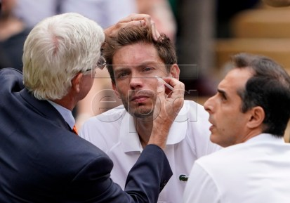 Nicolas Mahut (C) of France receives medical treatment during the Men's Doubles final match with Edouard Roger-Vasselin of France against Juan Sebastian Cabal of Colombia and Robert Farah of Colombia at the Wimbledon Championships at the All England Lawn Tennis Club, in London, Britain, 13 July 2019. EPA-EFE/NIC BOTHMA EDITORIAL USE ONLY/NO COMMERCIAL SALES