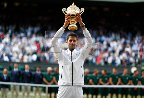 Novak Djokovic of Serbia hoists the championship trophy after defeating Roger Federer of Switzerland in the men's final of the Wimbledon Championships at the All England Lawn Tennis Club, in London, Britain, 14 July 2019. EPA-EFE/NIC BOTHMA EDITORIAL USE ONLY/NO COMMERCIAL SALES