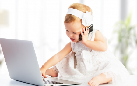 jobs for women Baby in all white sitting in front of a laptop holding a phone to her ear.