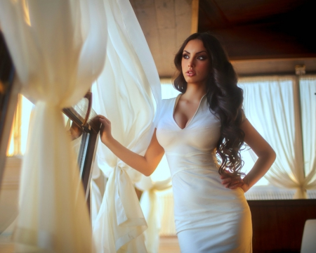 dating a maneater - exotic looking woman in white dress standing by the open window