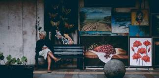 seniors getting a divorce older lady sitting on bench in front of artwork photo by Ali Yahya