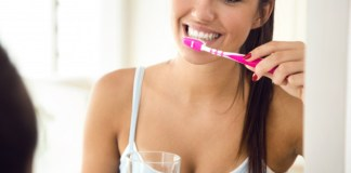 6 Dental Facts and Tips For A Healthier Smile pretty-young-woman-brushing-her-teeth-in-the-bathroom_1301-7648