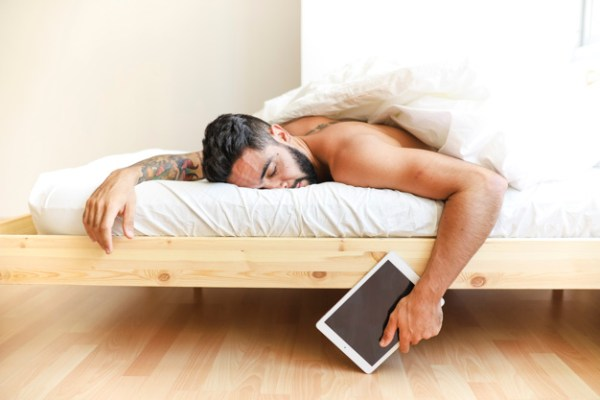 Top 11 Basic Self-Care Tips to Reduce Stress man-sleeping-on-bed-holding-digital-tablet_23-2147911954