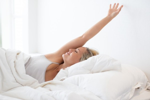 cbd oil happy-young-woman-stretching-bed-after-sleep_1262-5199