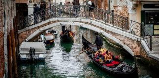 10 Things to Do in Venice as a Couple or Solo venice italy people in boats walking over bridge 1