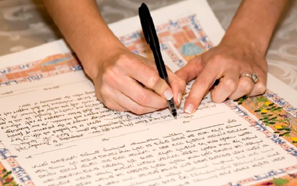 bride signing a jewish katuba marraige certificate