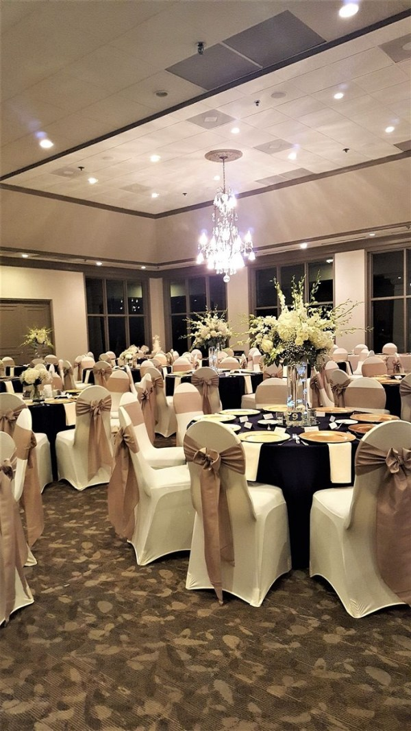 reception chairs with gold and burgundy colored ribbons