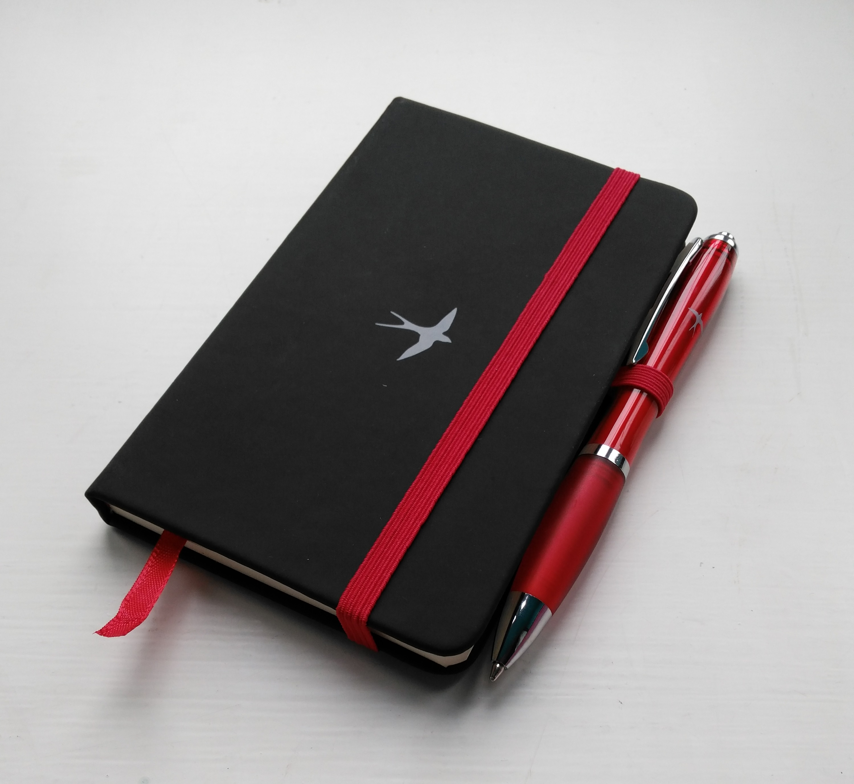 Notebook and Pen featuring Swallow logo