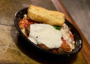 A takeout container of chicken parmigiana over pasta with a piece of garlic bread