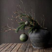 Bild: herberslifestyle.nl // Ein alter Zweig, ein Kiefernzweig, eine Lichterkette und 2 Baumkugeln schmücken deinen Tisch weihnachtlich