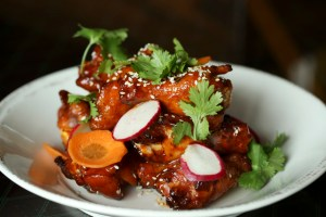 Smoked Springer Mountain chicken wings with gochujang pepper jelly, pickled carrots and sesame seeds.