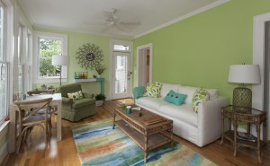 The sun room's yellow-green walls were inspired by a pair of pillows that Winburn had made from some old IKEA fabric (pictured on sofa and armchair).