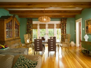 The use of natural wood and green paint is continued in a dining nook just off of the family room.