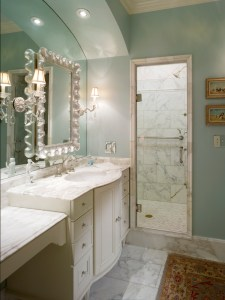 Pale blue walls, marble floors and white wood cabinetry come together to brighten up a spacious bath.
