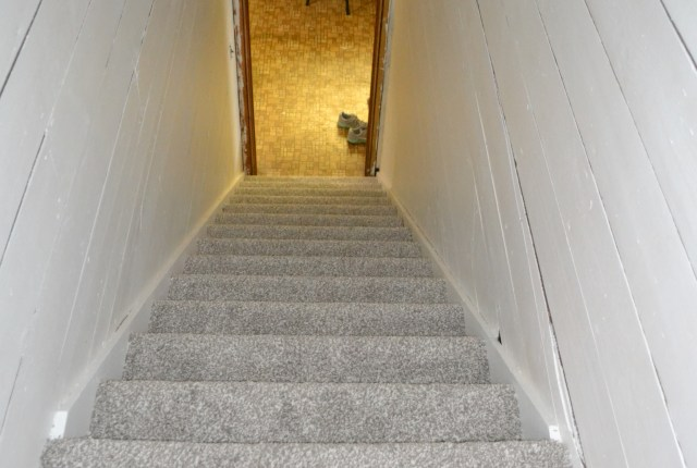 A view down a stariwell with original shiplap painted white and a grey carpet on the stairs