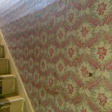 A side view up a stairwell with pink, white and teal flowered wallpaper