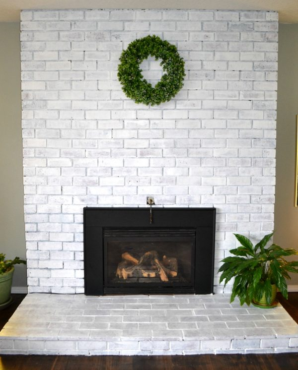 Looking straight on at a floor to ceiling brick fireplace that has been whitewashed with a gas fireplace insert and a green wreath hanging on the fireplace
