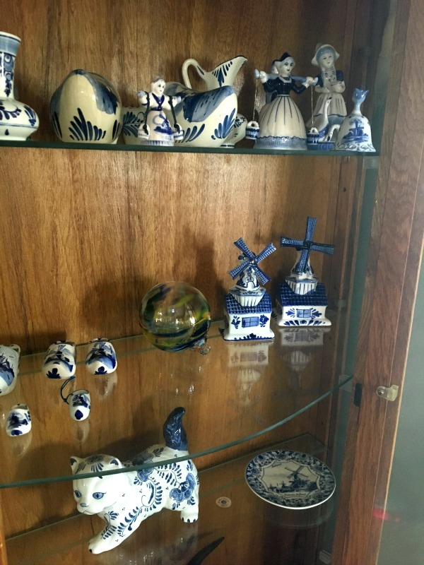 Delft blue figurines displayed in a curio cabinet