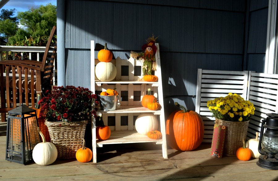 Front porch decor for the fall including white pumpkins and mums and thrift store baskets