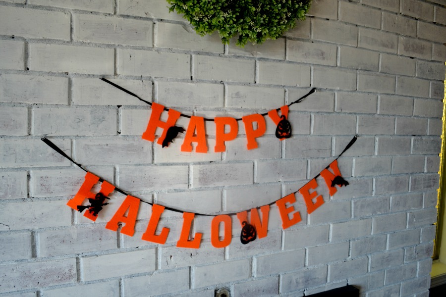 Felt Halloween sign displayed on a living room fireplace