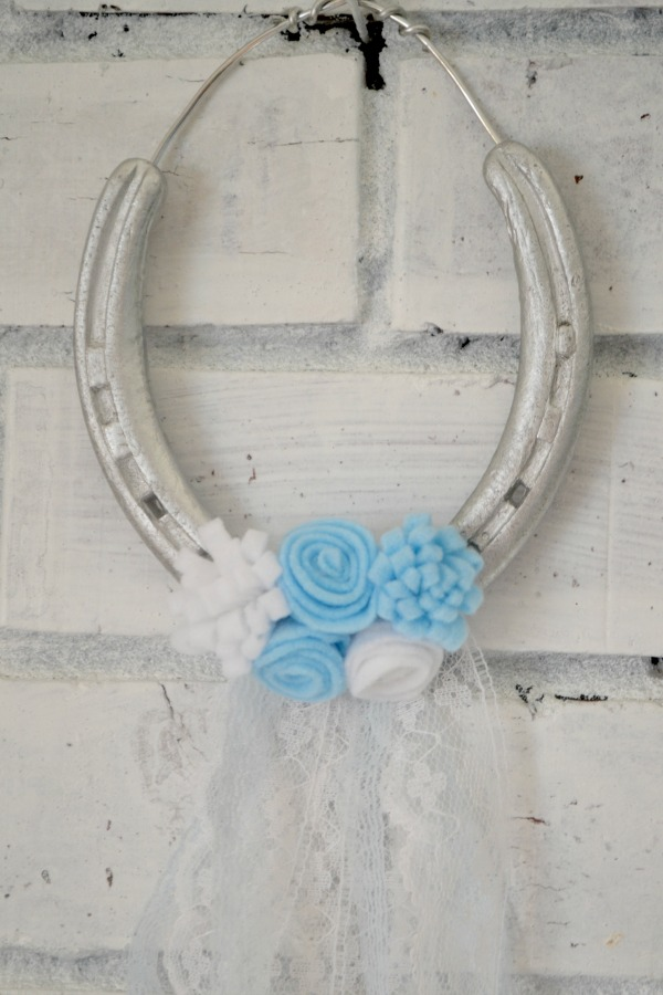 Turn old horseshoes into a pretty boho hanging decor with some felt flowers and lace