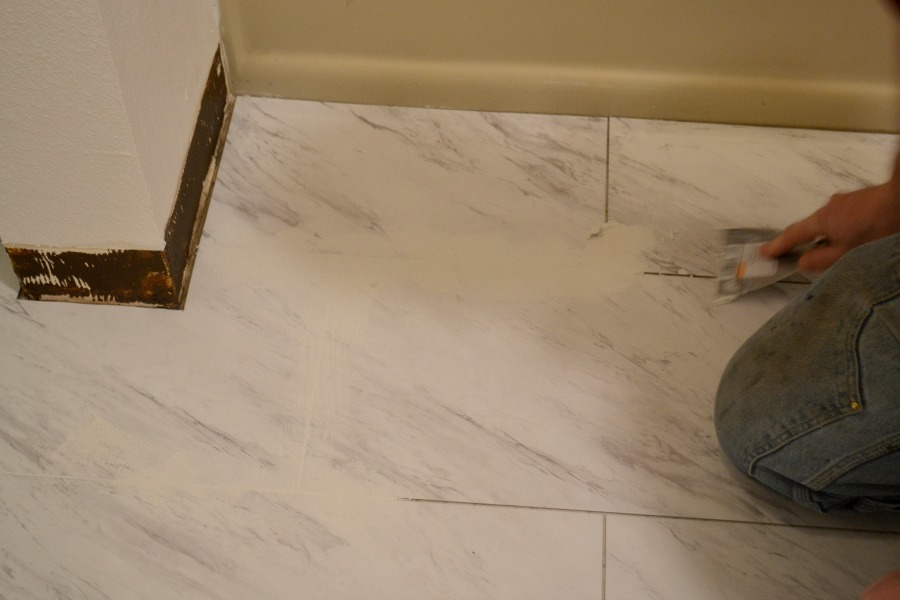 Applying grout to carerra marble tiled floor