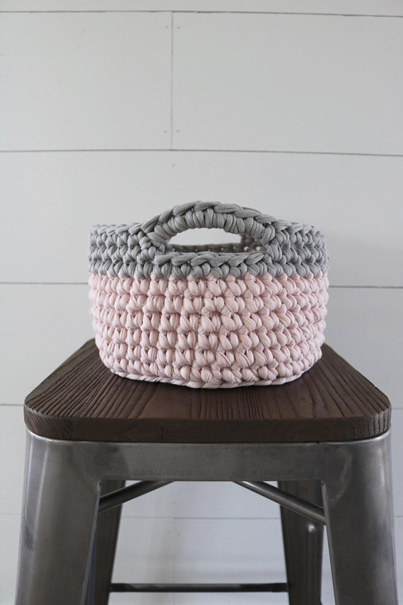 A crocheted basket in pink and grey sitting on a wood stool with a shiplap background