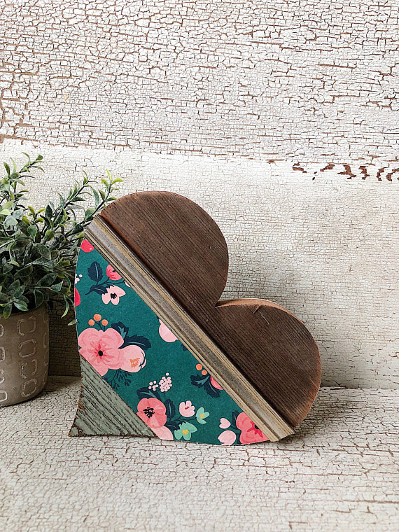 A wood heart that is pieced together with different types of woods and wallpaper sitting on it's side