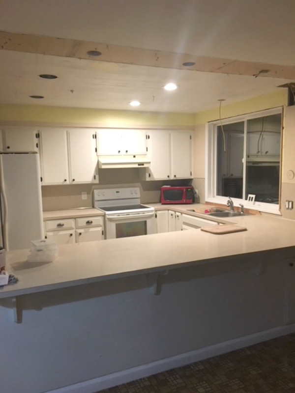 A side view of a kitchen with clean countertops and new can ligths installed