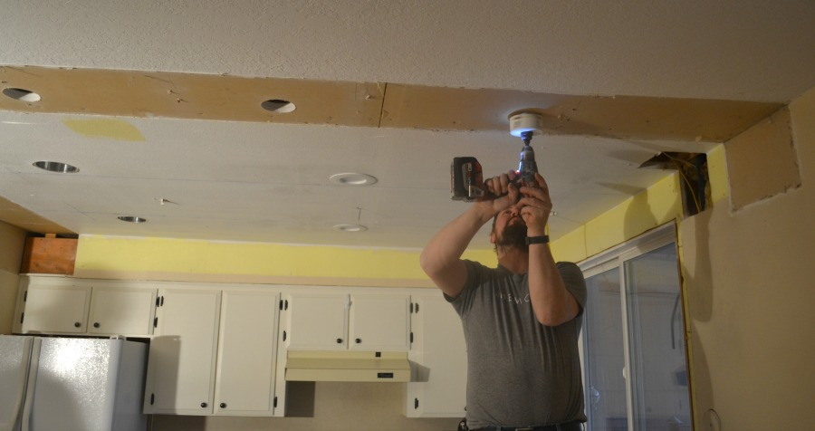 A man using a smaller hole saw to drill holes over the kitchen island for pendant lights
