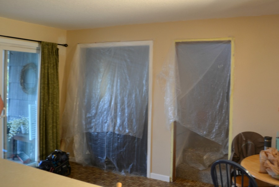 View from the kitchen to a dining room and stairwell that are covered with plastic sheeting