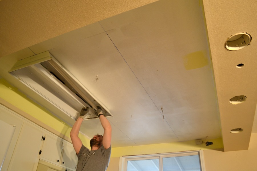 Looking at a man from the floor toward the ceiling as he removes a metal fluroescent light cover