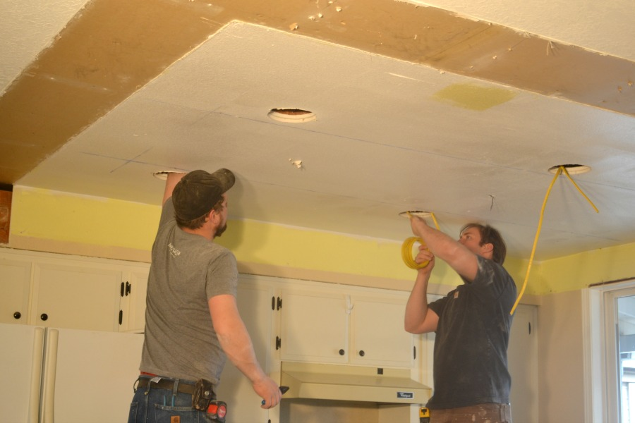 Two men pulling wire through drilled holes in the ceiling