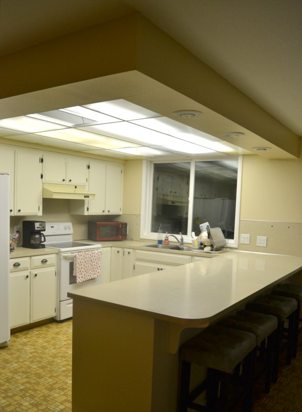 A side view of a kitchen with a u-shape and a long island with a 1 foot drop ceiling above with fluorescent lights