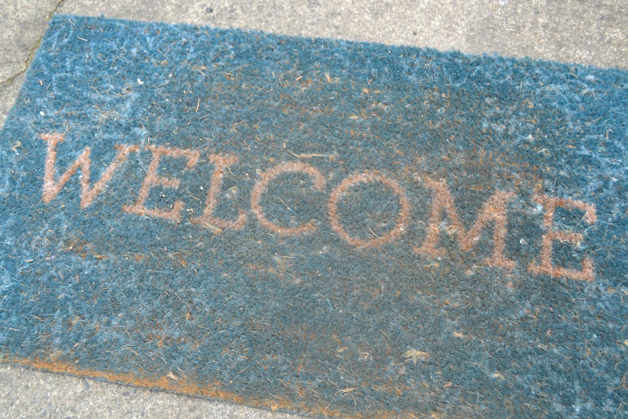 A blue welcome mat with the word welcome, mat is worn and dirty
