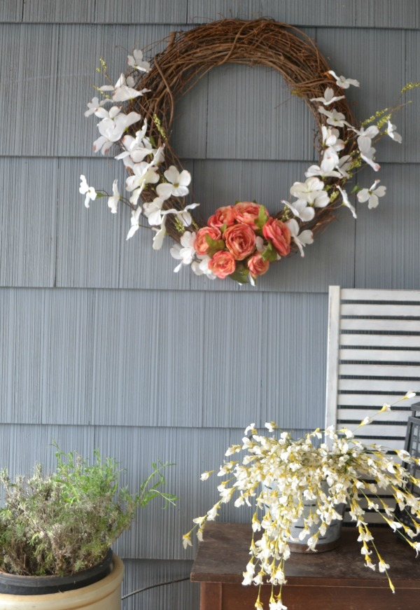 A grapevine wreath with faux flowers on the lower half hung on a blue house with a lavendar plant below next to a stool with a lantern and faux flowers